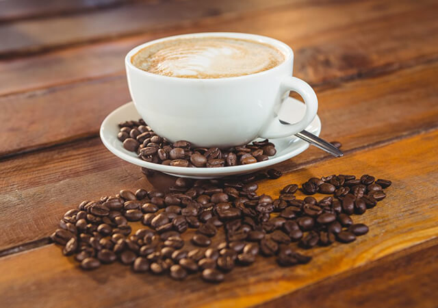 Cappuccino-with-coffee-beans-on-table-in-cafeteria-640x450
